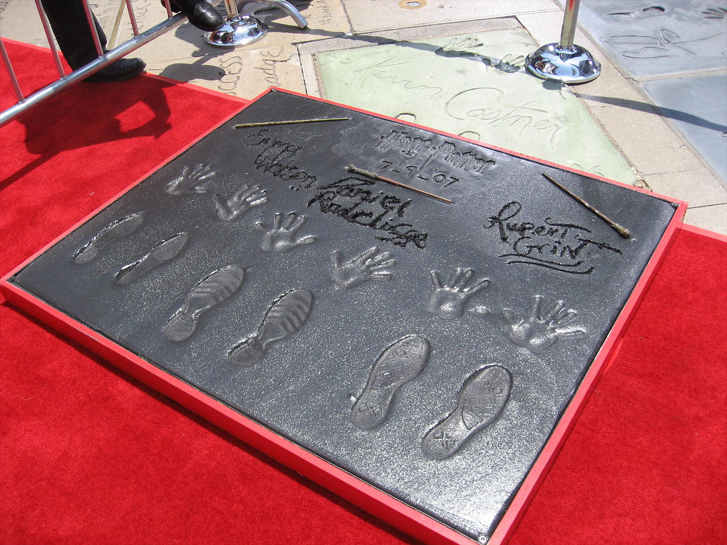 Dan, Rupert and Emma imprint their hands, feet and wands in concrete