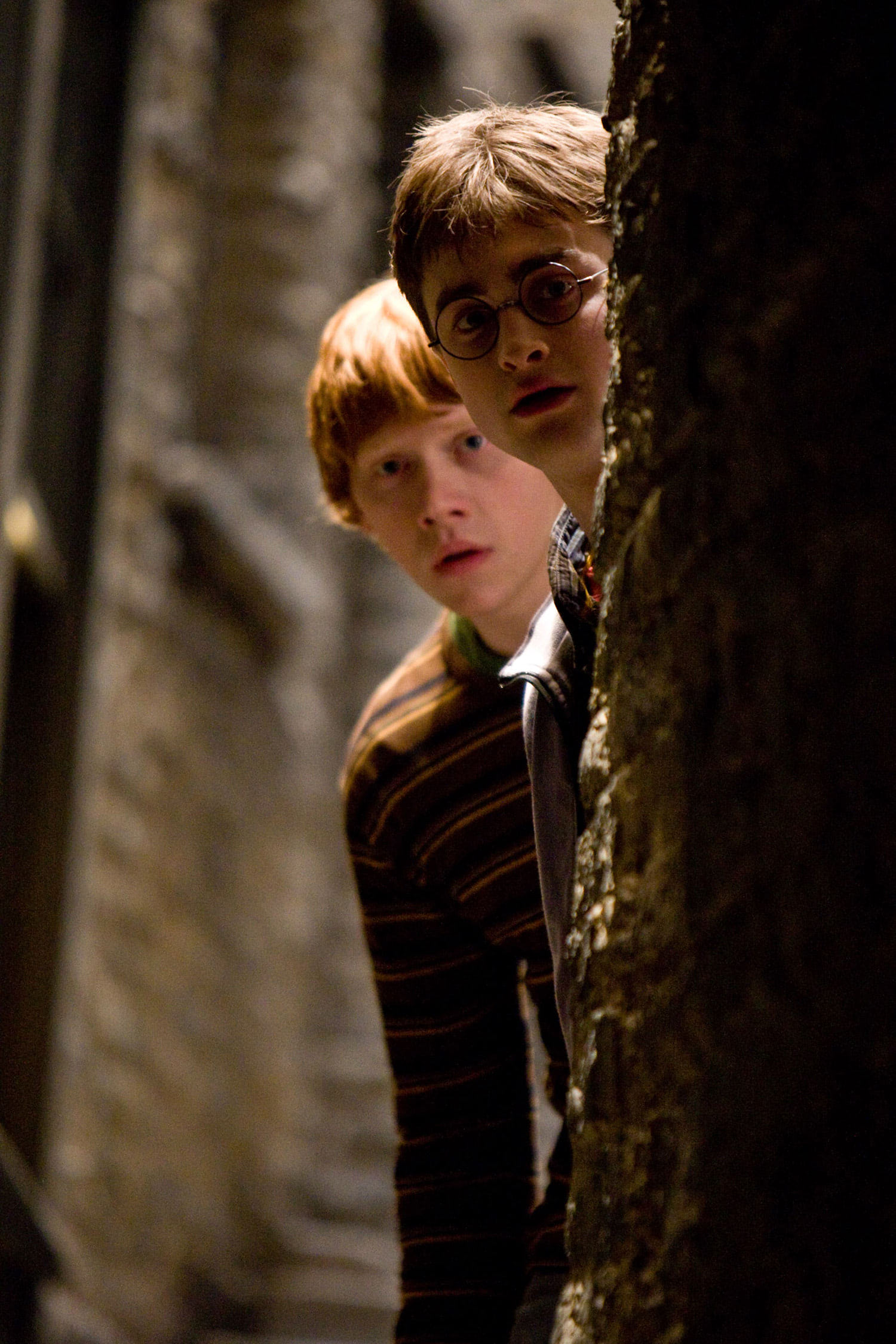 Harry and Ron look out from behind a wall