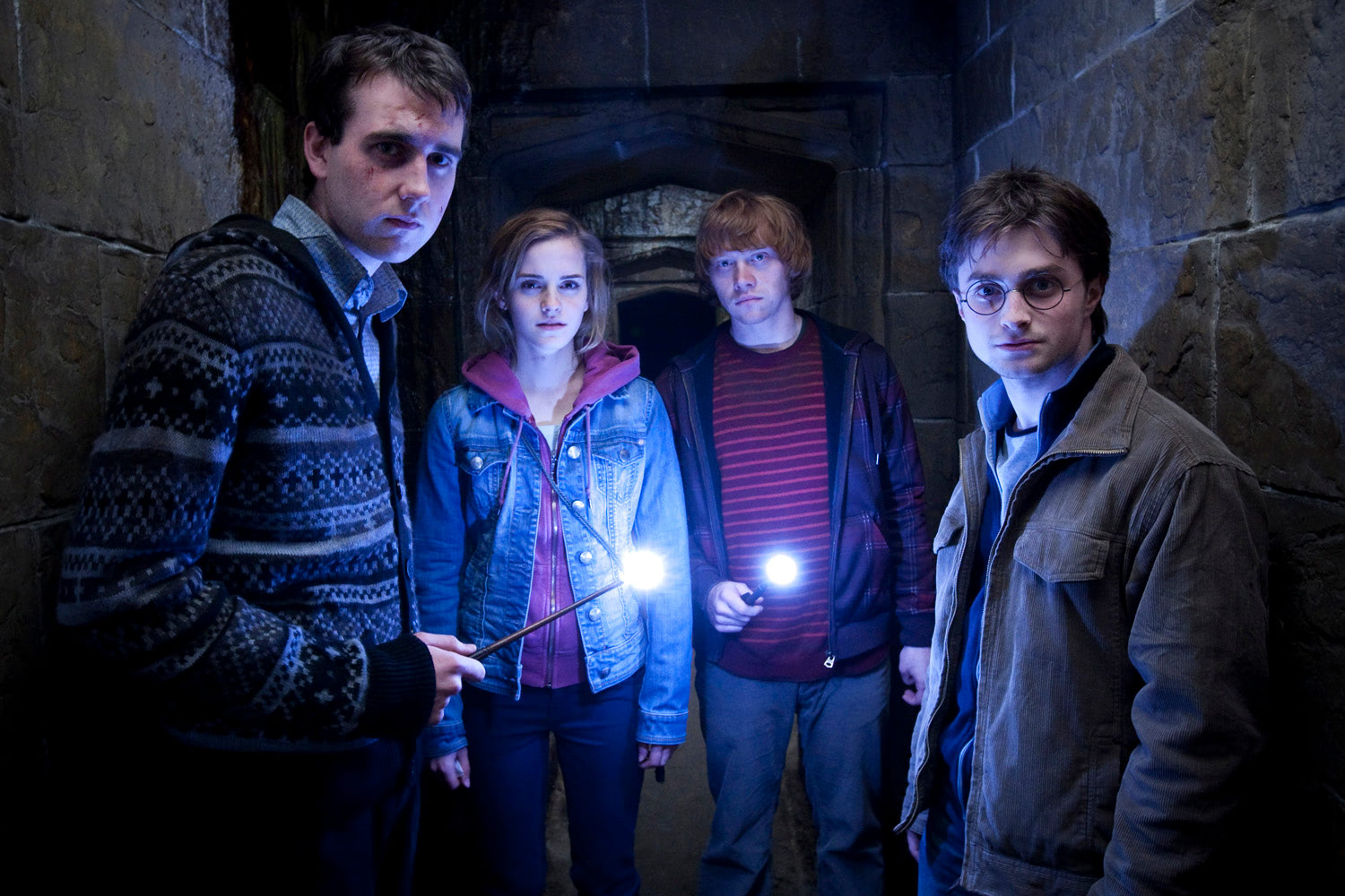 Neville, Hermione, Ron and Harry with wands alight