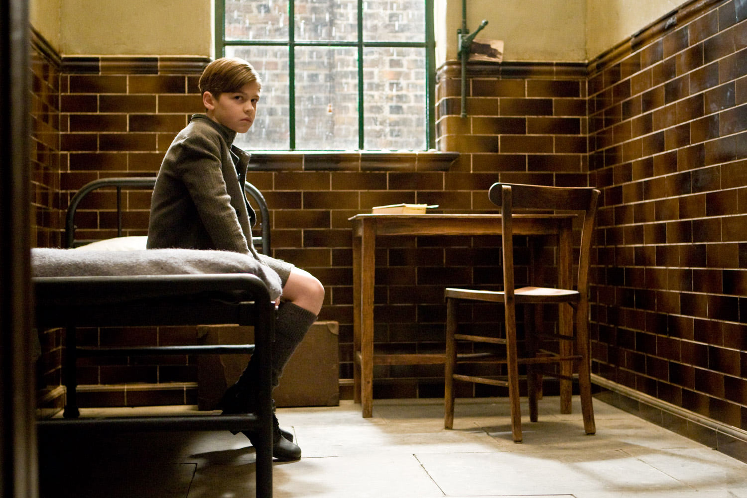 Tom Riddle sits on his bed